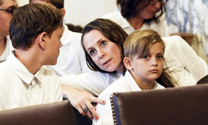 Leslie Danesi, center, sits with her children Lorenzo Danesi, left, and Gabriel Danes, right, as attorneys prepare to speak at a hearing challenging the constitutionality of the state legislature's repeal of the religious exemption to vaccination in Albany, N.Y. on Aug. 14, 2019.