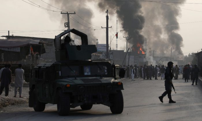 Policemen keep watch as angry Afghan protesters burn tires and shout slogans at the site of a blast in Kabul, Afghanistan on Sept. 3, 2019. (Omar Sobhani/Reuters)