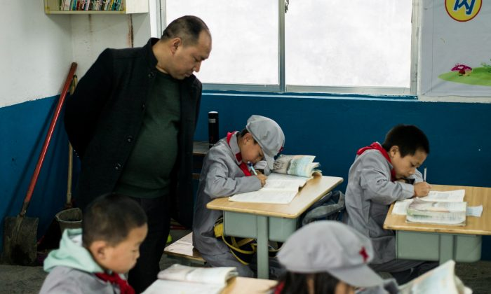 "A teacher supervises students in the Yang Dezhi ""Red Army"" elementary school in Wenshui, Xishui County in Guizhou Province, China on Nov. 7, 2016. In 2008, Yang Dezhi was designated a ""Red Army primary school""—such schools are an extreme example of the ""patriotic education"" which China's ruling Communist party promotes to boost its legitimacy, but which critics condemn as little more than brainwashing. (Fred Dufour/AFP/Getty Images)"