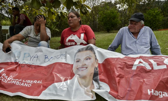 Relatives and friends of murdered mayoral candidate Karina Garcia mourn over a banner advertising her campaign in Suarez, Cauca, Colombia, on Sept. 2, 2019.  (Luis Robayo/AFP/Getty Images)
