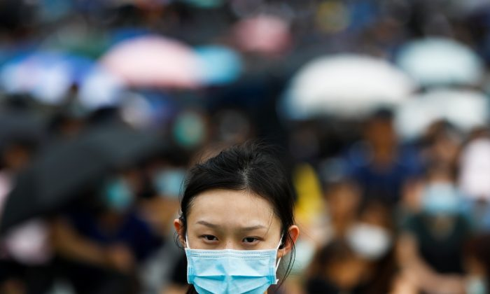 A protester covers her face with a mask during a general strike at Tamar Park in front of the government buildings in Hong Kong, on Sept. 3, 2019. (Kai Pfaffenbach/Reuters)
