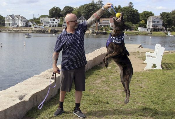 Former U.S. Navy SEAL James Hatch plays with his service dog,
