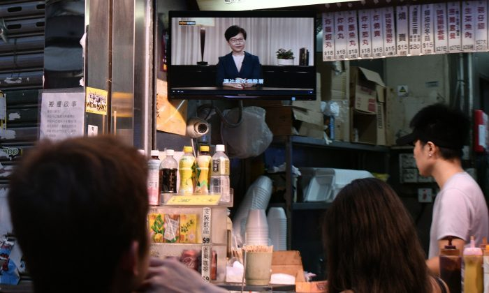 Customers at an eatery watch a live television broadcast showing Hong Kong Chief Executive Carrie Lam formally withdrawing a controversial extradition bill in Hong Kong on September 4, 2019. (ANTHONY WALLACE/AFP/Getty Images)