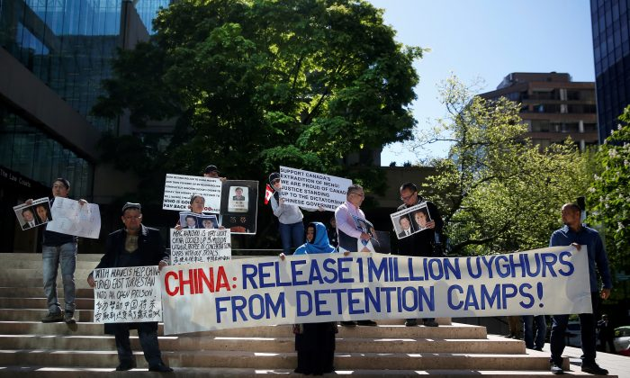 People hold signs protesting China's treatment of the Uyghur people during a court appearance by Huawei's Financial Chief Meng Wanzhou, outside of British Columbia Supreme Court building in Vancouver, British Columbia, Canada on May 8, 2019. (Lindsey Wasson/Reuters)