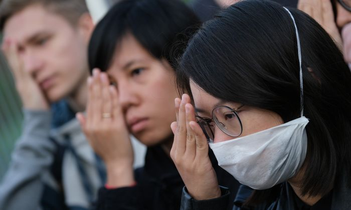 Protesters standing outside the Chancellery cover one eye in reference to an injured demonstrator in Hong Kong as they urge German Chancellor Angela Merkel to show solidarity with pro-democracy demonstrations in Hong Kong on Sept. 5, 2019, in Berlin, Germany. (Sean Gallup/Getty Images)