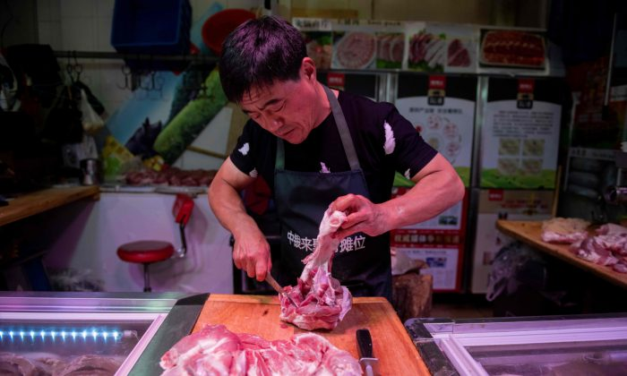 A butcher cuts a piece of pork meat at his stall at a market in Beijing, China, on July 10, 2019. (Nicolas Asfouri/AFP/Getty Images)