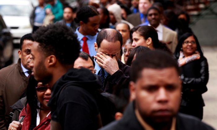 A man rubs his eyes as he waits in a line of job seekers, to attend the Dr. Martin Luther King Jr. career fair held by the New York State department of Labor in New York on April 12, 2012. (Lucas Jackson/Reuters)