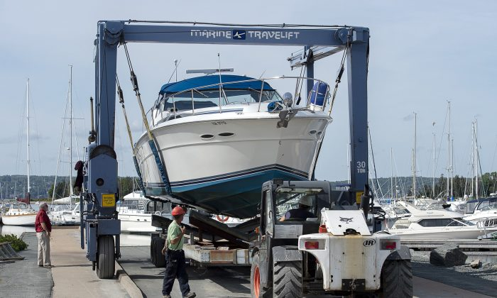 Workers haul boats from the water at the Dartmouth Yacht Club in Dartmouth, N.S., on Sept. 6, 2019, as they prepare for the arrival of Hurricane Dorian. The major storm is expected to hit Nova Scotia on Saturday. (THE CANADIAN PRESS/Andrew Vaughan)