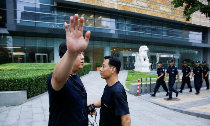 A police officer gestures at the photographer as security patrol outside the headquarters of China Banking and Insurance Regulatory Commission (CBIRC) in Beijing, China on Aug. 6, 2018. (Thomas Peter/Reuters)