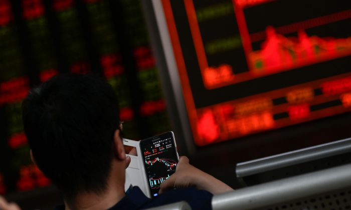 An investor looks at his mobile phone showing stock market movements at a securities company in Beijing  on May 14, 2019. (Wang Zhao/ AFP/Getty Images)