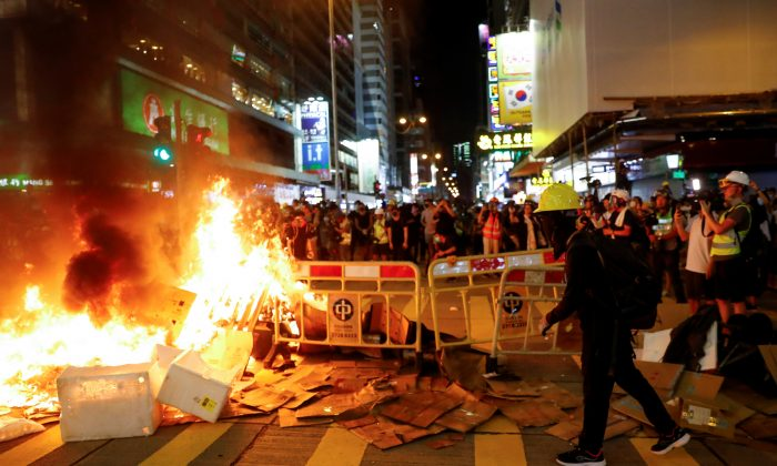 Protestors stand behind a burning barricade during a demonstration in Mong Kok district in Hong Kong, China on Sept. 6, 2019. (Kai Pfaffenbach/Reuters)
