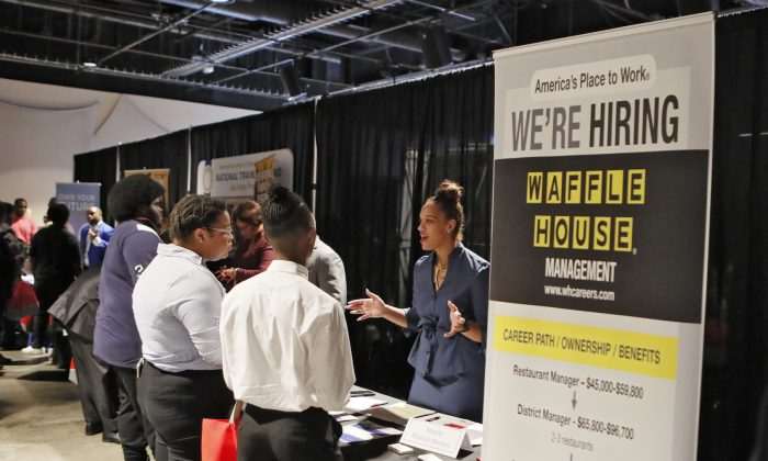 A Waffle House representative speaks to potential applicants during a job and resource fair in Atlanta on Aug. 14, 2019. (Bob Andres/Atlanta Journal-Constitution via AP/)
