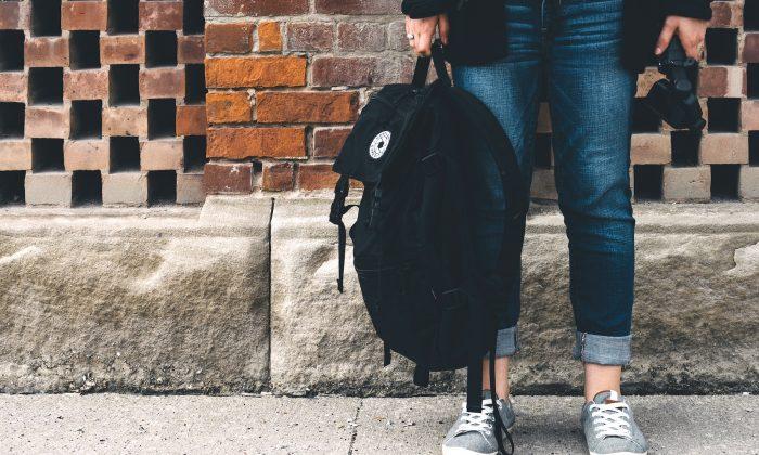 Illustration photo of person holding backpack. (@scottwebb/Unsplash)