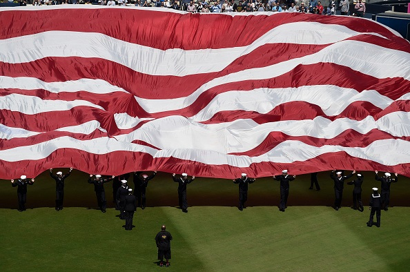 U.S. Navy sailors bring a giant American flag onto the field before the game between the San Diego Padres and the San Francisco Giants