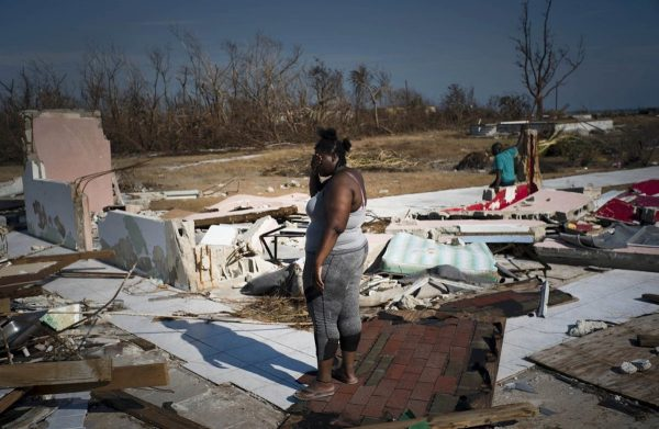 Woman looks at house destroyed by Hurricane Dorian