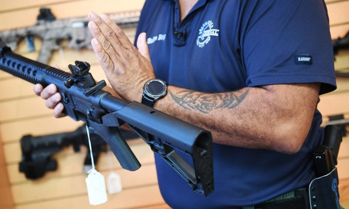 A man shows a bump stock installed on an AR-15 rifle at Blue Ridge Arsenal in Chantilly, Virginia, on Oct. 6, 2017. Some Democratic presidential candidates are pushing for a ban on assault weapons, with a few advocating for so-called mandatory buybacks. (Jim Watson/AFP/Getty Images)
