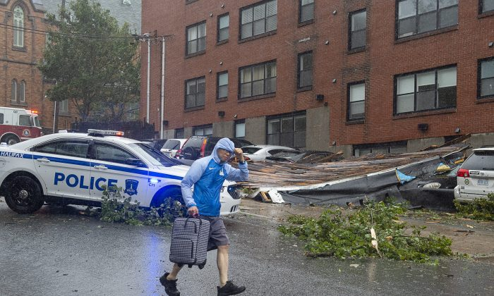 A man heads past part of an apartment roof that landed on several cars in Halifax as hurricane Dorian approaches on Sept. 7, 2019. (The Canadian Press/Andrew Vaughan)