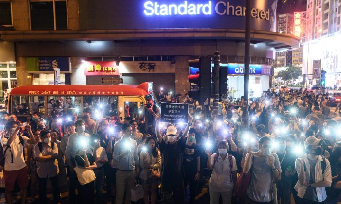 Protesters use the light of their mobile phones as they gather outside the Mong Kok police station in Hong Kong on Sept. 7, 2019. (Philip Fong/AFP/Getty Images)