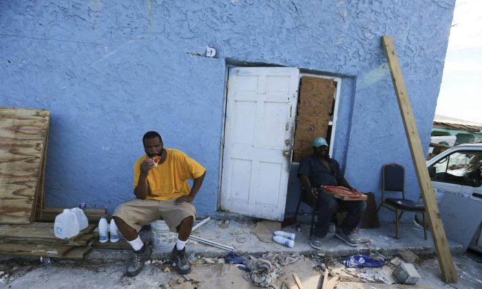 Men eat pizza delivered by volunteers, at a town destroyed by Hurricane Dorian in Marsh Harbor, Abaco Island, Bahamas, on Sept. 6, 2019. (Fernando Llano/AP Photo)