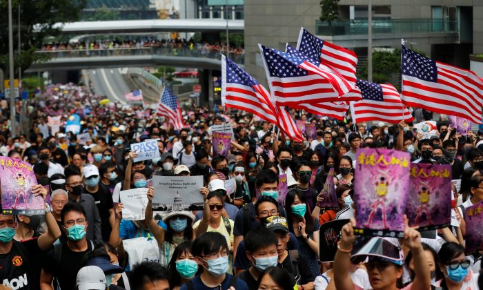 Protesters hold U.S. flags during a march to the U.S. Consulate General in Hong Kong, China, on Sept. 8, 2019. (Anushree Fadnavis/Reuters)