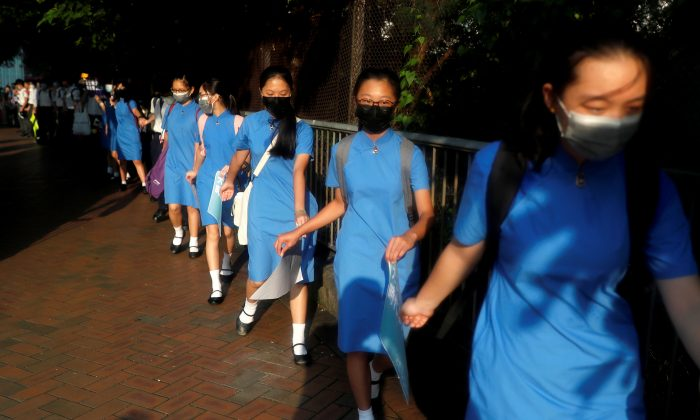 Secondary school students hold hands as they form a human chain as they demonstrate against what they say is police brutality against protesters, after clashes at Wan Chai district, in Hong Kong, China on Sept. 9, 2019. (Amr Abdallah Dalsh/Reuters)