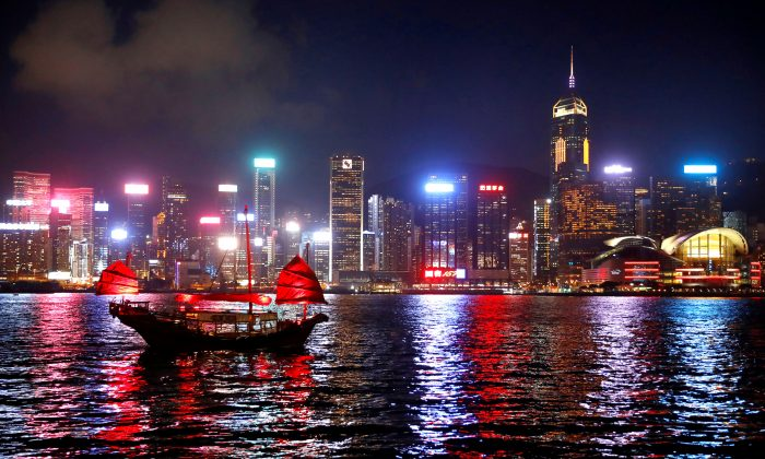A junk boat passes the skyline as seen from the Tsim Sha Tsui waterfront in Hong Kong, China on Aug. 27, 2019. (Kai Pfaffenbach/Reuters)