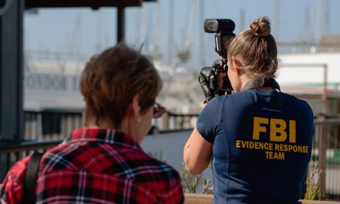 An FBI photographer takes evidence pictures as authorities search the Truth Aquatics' offices, the California company that owned the scuba diving boat that caught fire and killed dozens of people last week, on the Santa Barbara Harbor in Santa Barbara, Calif., on Sept. 8, 2019. (Christian Monterrosa/AP Photo)