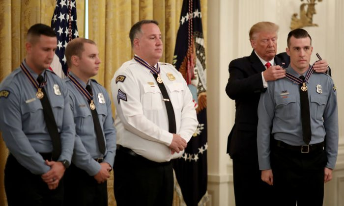 President Donald Trump presents the Medal of Valor to Officer David Denlinger of the Dayton Police Department during a White House ceremony in Washington on Sept. 9, 2019. (Win McNamee/Getty Images)