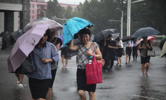 Pedestrians shield themselves from wind and rain brought by Typhoon Lingling Saturday, Sept. 7, 2019, in Pyongyang, North Korea. (AP Photo/Jon Chol Jin)