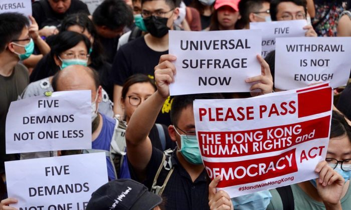 Protesters hold up different signs during a march to the U.S. consulate in Hong Kong on Sept. 8, 2019. (Yu Gang/The Epoch Times)