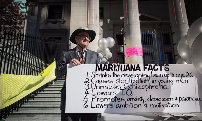 A man holds a sign during a protest about the dangers of marijuana in Vancouver on the day recreational cannabis became legal, Oct. 17, 2018. (THE CANADIAN PRESS/Darryl Dyck)