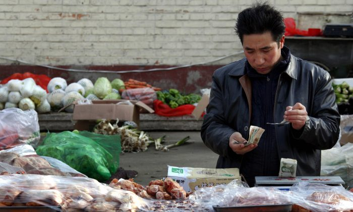 Fruit and vegetables can be seen behind a man selling pork as he checks his money at a small roadside market in central Beijing, China on March 1, 2011. (David Gray/Reuters)