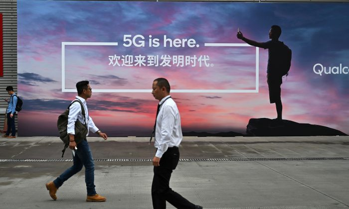 People walk past a poster advertising 5G internet at the Mobile World Congress (MWC 2019) introducing next-generation technology at the Shanghai New International Expo Centre (SNIEC) in Shanghai on Jun. 26, 2019. (Hector Retamal/AFP/Getty Images)