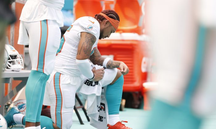 Albert Wilson #15 of the Miami Dolphins kneels during the playing of the national anthem prior to the game against the Baltimore Ravens at Hard Rock Stadium in Miami, Florida, on Sept. 8, 2019. (Michael Reaves/Getty Images)