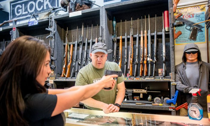 In this file image, Edward Wilks shows a gun to  at  his store in Rifle, Colorado on April 24, 2018. (Emily Kask /AFP/Getty Images)