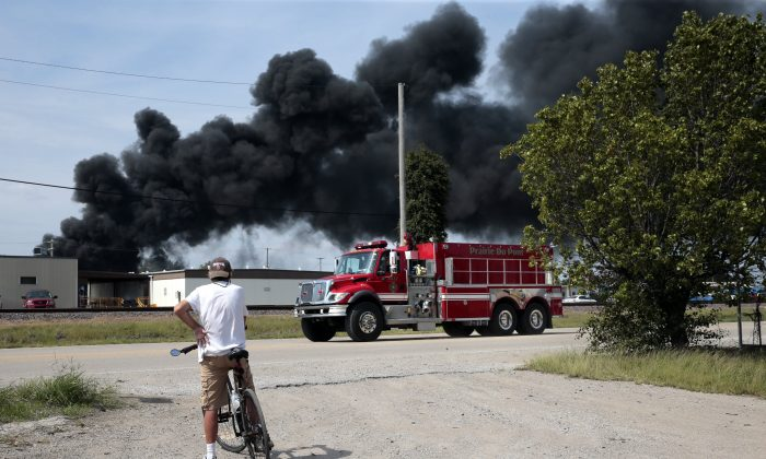 A resident watches as a firetruck arrives in downtown Dupo, Ill. to help fight a tanker fire from a derailed train on Sept. 10. 2019. (Robert Cohen/St. Louis Post-Dispatch via AP)