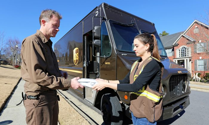 A young seasonal worker (R) helps deliver a parcel for UPS. (Courtesy of UPS)