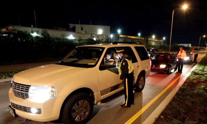 RCMP officers look for impaired drivers during a roadside check in Surrey, B.C., in a file photo. (The Canadian Press/Darryl Dyck)