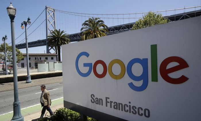 A man walks past a Google sign outside with a span of the Bay Bridge at rear in San Francisco on May 1, 2019. (Jeff Chiu/AP Photo)