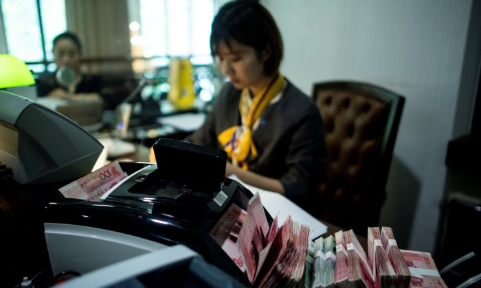 A bank employee uses a money counting machine to count out 100 yuan notes at a bank in Shanghai on Aug. 8, 2018.  (Johannes Eisele/AFP/Getty Images)