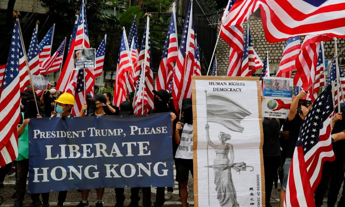 Protesters hold signs and U.S. flags during a rally in Hong Kong, China September 8, 2019. REUTERS/Anushree Fadnavis