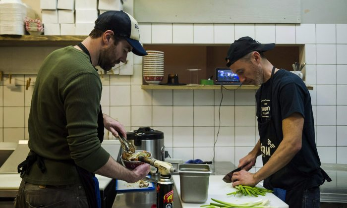 Restaurant workers are typically among the many youth working minimum wage jobs. The 2018 increases in the minimum wage have forced restaurant owners into making difficult decisions to either cut staff, raise prices, or absorb the extra costs. (The Canadian Press/Christopher Katsarov)