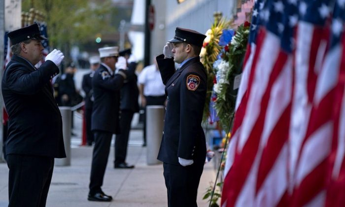 New York City firefighters salute in front of a memorial on the side of a firehouse adjacent to One World Trade Center and the 9/11 Memorial site during ceremonies on the 18th anniversary of 9/11 terrorist attacks in New York on Sept. 11, 2019. (Craig Ruttle/AP Photo)