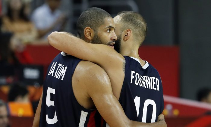 Basketball - FIBA World Cup - Quarter Finals - United States v France - Dongguan Basketball Center, Dongguan, China - Sept. 11, 2019. France's Nicolas Batum and Evan Fournier celebrate victory after the match. (Kim Kyung-Hoon/Reuters)