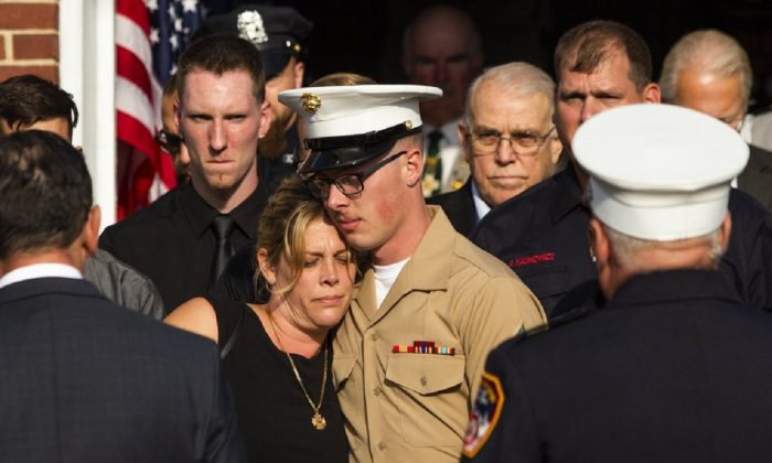 Erika Starke, left, is comforted by her son Michael Haub as they attend a second funeral service for New York Fire Department firefighter Michael Haub, in Franklin Square, N.Y., Sept. 10, 2019. (Eduardo Munoz Alvarez/AP Photo)