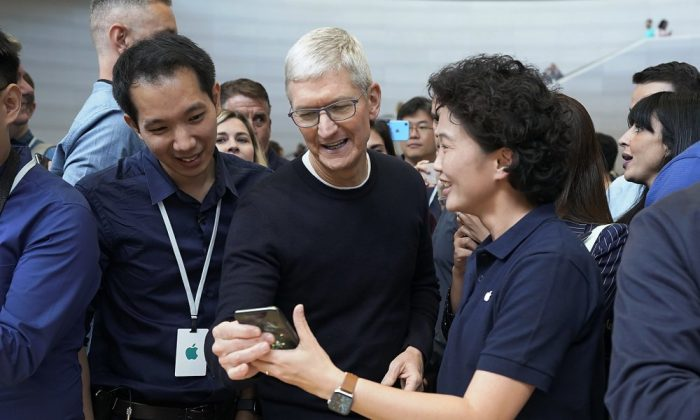 Apple CEO Tim Cook, center, looks at the the new iPhone 11 Pro Max, during an event to announce new products Tuesday, Sept. 10, 2019, in Cupertino, Calif. (AP Photo/Tony Avelar)
