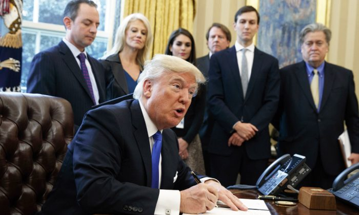 President Donald Trump signs an executive order on the Keystone XL pipeline in the Oval Office of the White House. Native American tribes in Montana and South Dakota say the Trump administration unlawfully approved the oil pipeline without considering potential damage to cultural sites. (Evan Vucci/AP)