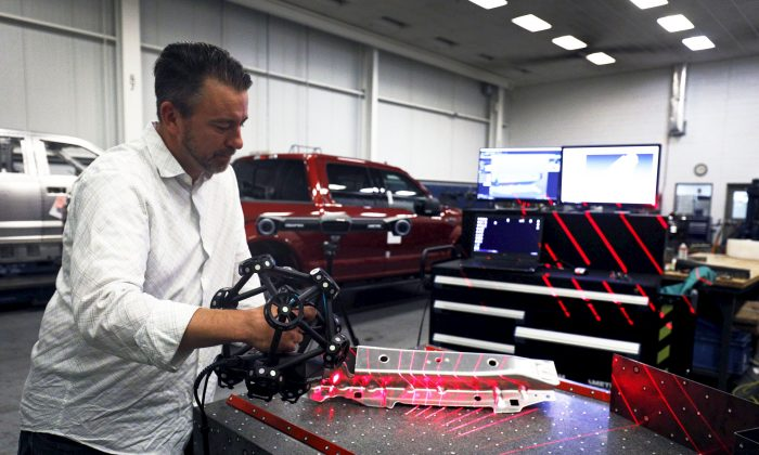 A Ford Motor Company worker operates a Creaform laser scanning measuring device at the Ford Dearborn Truck Plant in Dearborn, Mich., on Sept. 27, 2018. (Bill Pugliano/Getty Images)