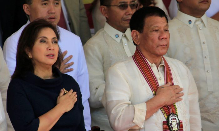 President Rodrigo Duterte and Vice-President Leni Robredo stand at attention for the national anthem during the Philippine National Police Academy (PNPA) graduation ceremony in Camp Castaneda, Silang town in Cavite city, Philippines on March 24, 2017. (Romeo Ranoco/Reuters)
