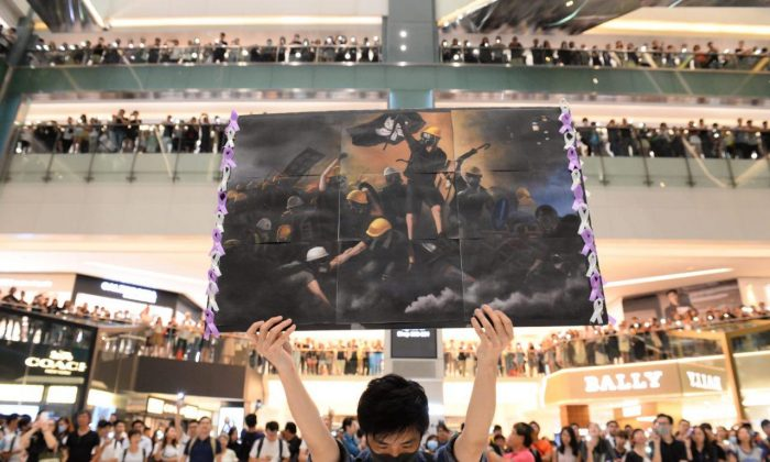 A man holds a poster at a shopping mall in the Sha Tin area of Hong Kong on Sept. 11, 2019, to sing a recently penned protest song titled 'Glory to Hong Kong which has been gaining popularity in the city. (Huang Xiaoxiang/The Epoch Times)